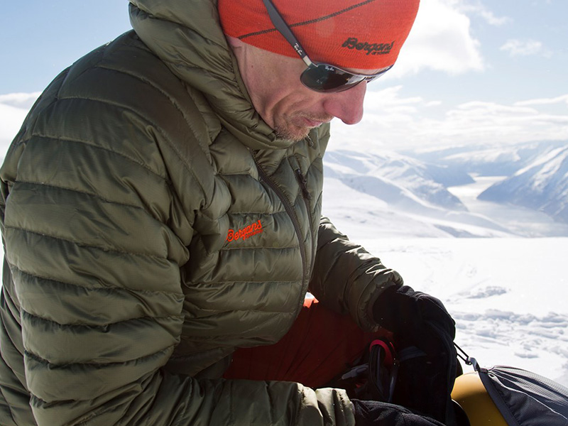 Мъж в снежната планина с пухено яке с качулка Bergans Slingsbytind Down Jacket w/Hood