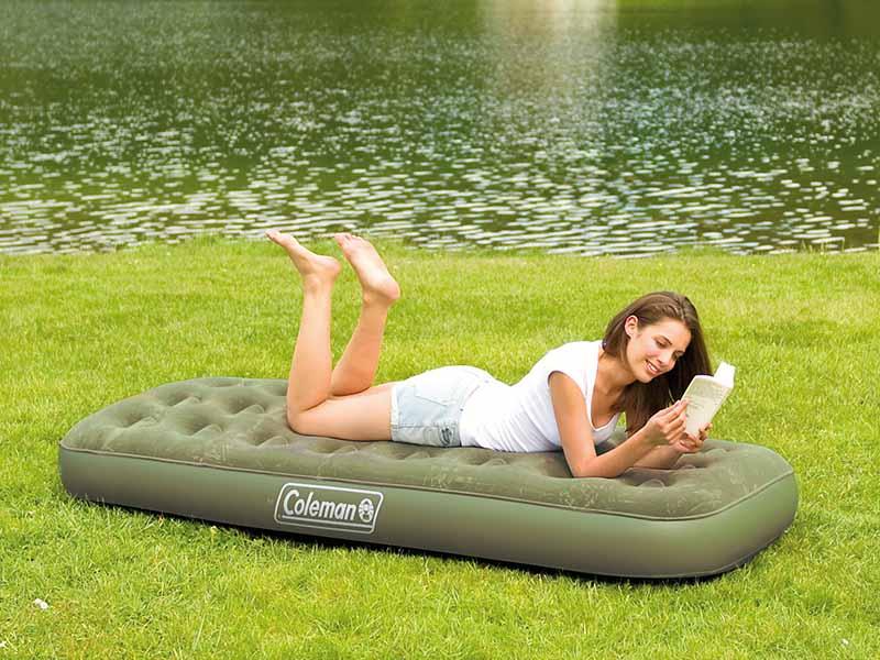 жена чете книга на надуваемо легло