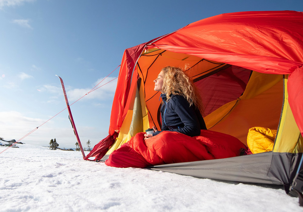 Cecilie sitting on the porch of HELIUM EXPEDITION DOME 2-PERSONS TENT